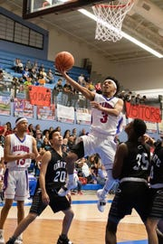 Las Cruces High's Marcus Scott splits the defenders on his way to the basket. Las Cruces High School played Oñate  High School for the district championship on Friday.