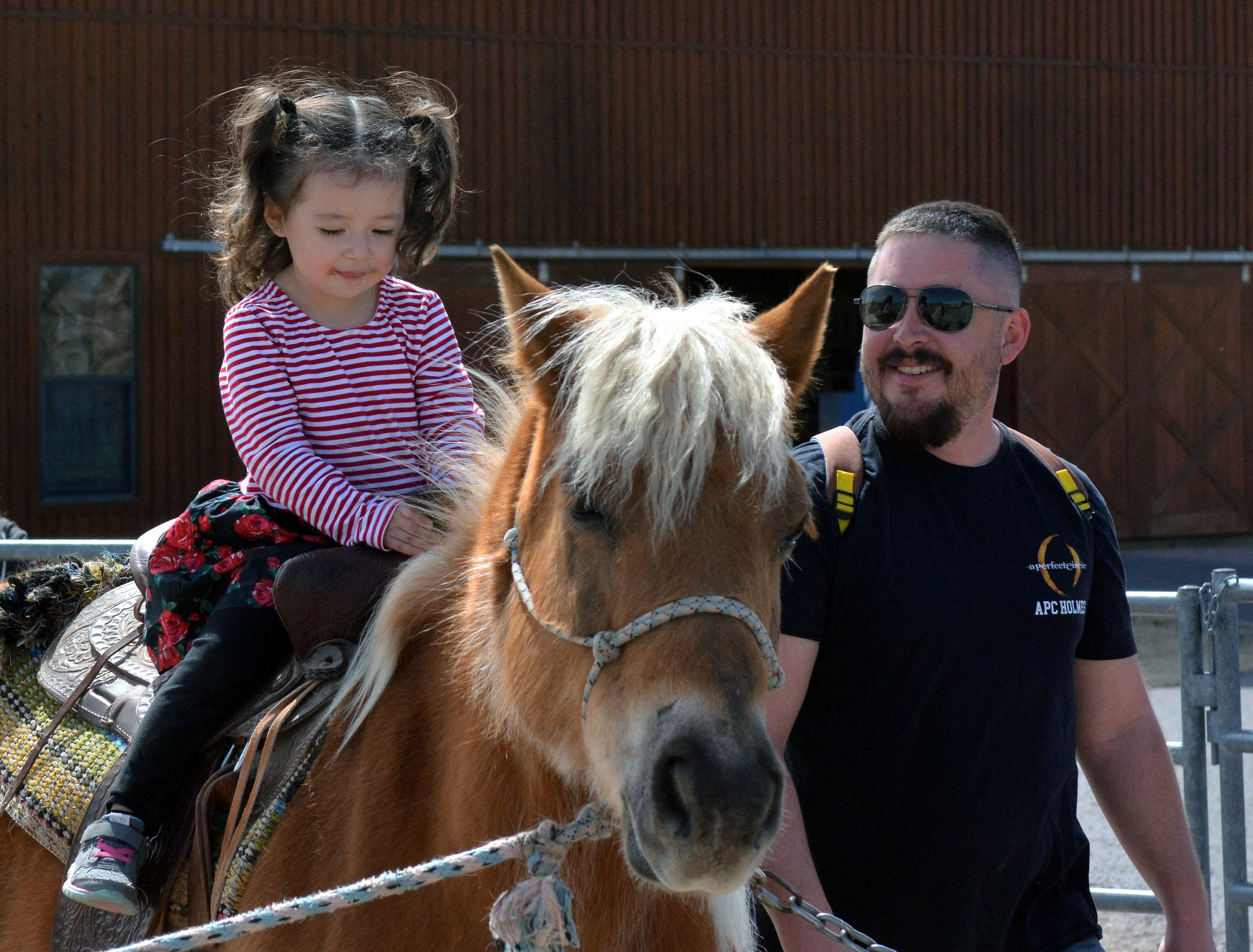 Isabella Stroller celebrates her third birthday by riding a horse for the first time as her father Josh Stroller walks by her side during the 20th annual Cowboy Days held Saturday, March 2, 2019, at the New Mexico Farm and Ranch Heritage Museum.