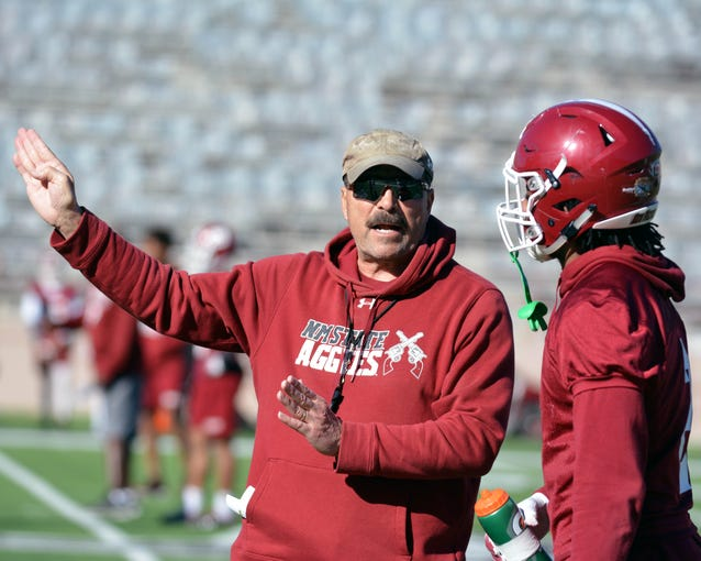 New Mexico State defensive coordinator Frank Spaziani instructs defensive back Chris Bell during spring workouts at Aggie Memorial Stadium.