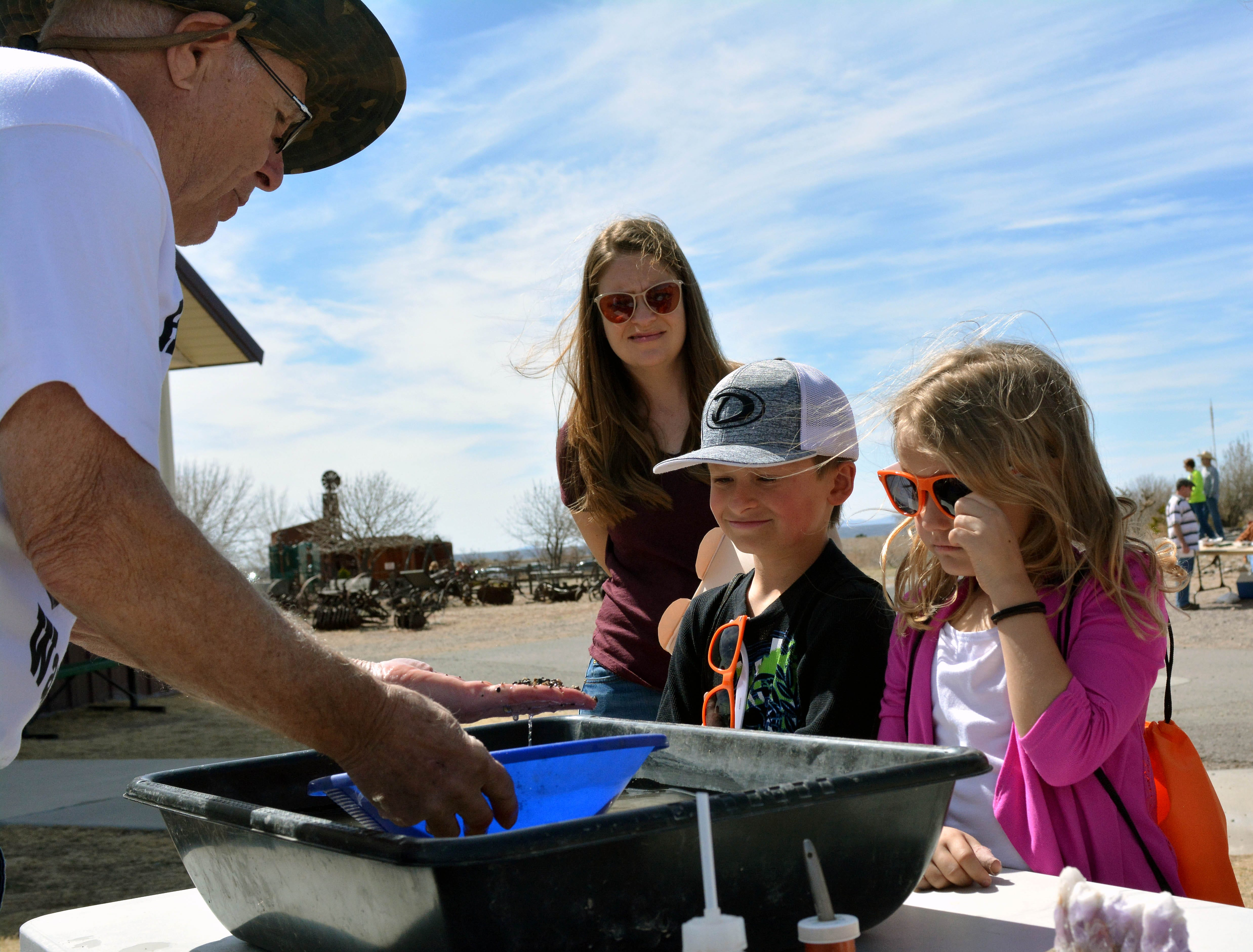 New Mexico Gold Prospectors member JIm Frederick shows Jenni Kosni, from left, Grady Cline and Presley Hart how to pan for gold during the 20th annual Cowboy Days held Saturday, March 2, 2019, at the New Mexico Farm and Ranch Heritage Museum.