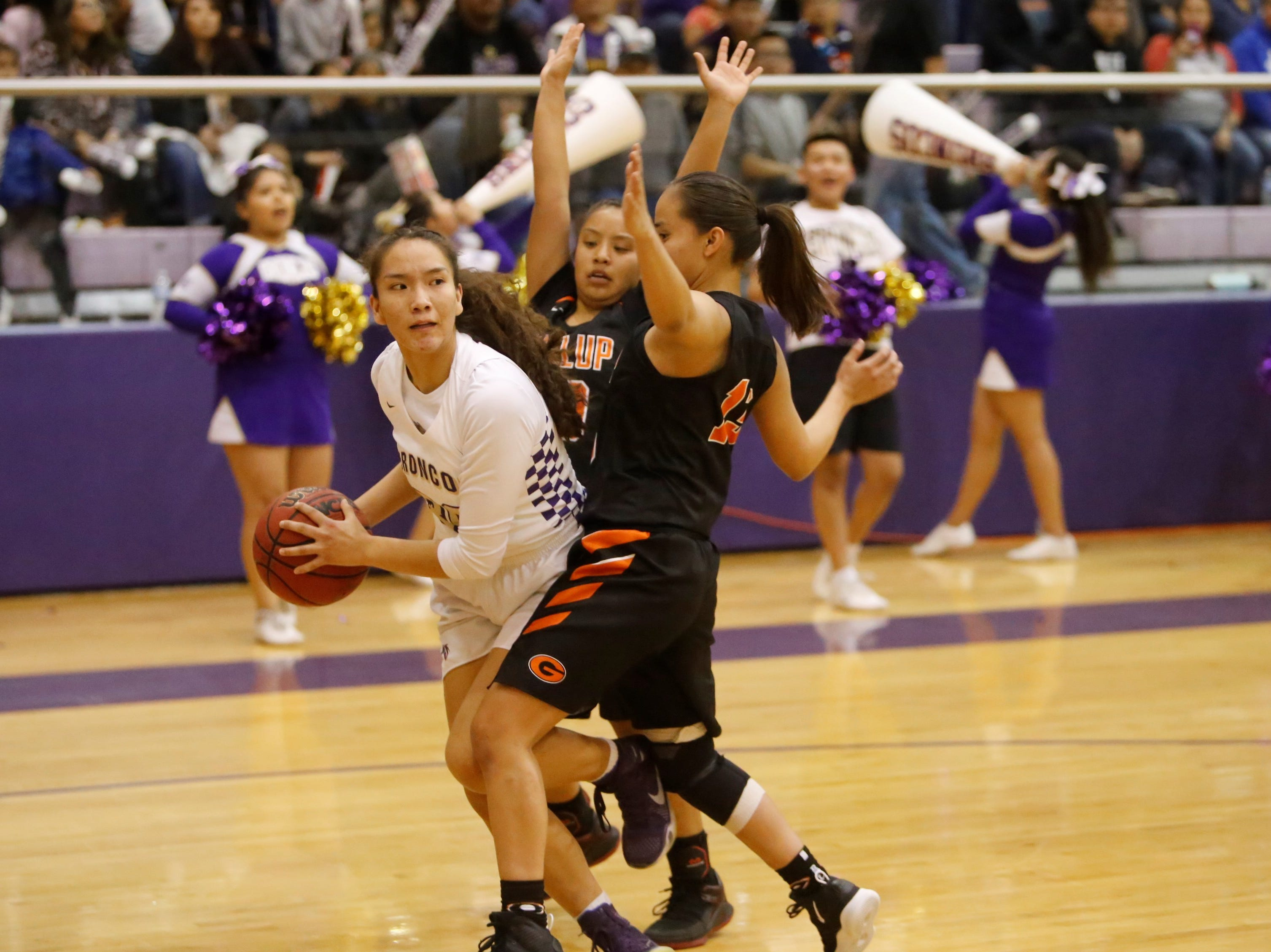 Kirtland Central's Siigrid Lii'bilnaghahi looks to pass the ball along the baseline against Gallup's Kamryn Yazzie (20) and Hanna Toledo (13) during Friday's District 1-4A tournament championship game at Bronco Arena.