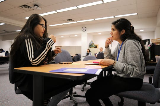 Client Charnell Williams, left, talks with San Juan College student Whitney Blue Eyes, right, about her income tax paperwork Friday at the Quality Center for Business. The Four Corners Tax Help is offering free income tax preparation.
