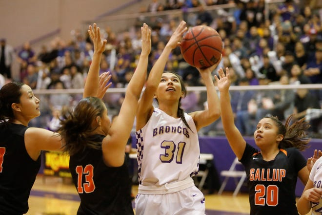 Kirtland Central's Tiajhae Nez puts up a shot against Gallup's Hannah Toledo (13) and Kamryn Yazzie (20) during Friday's District 1-4A tournament championship game at Bronco Arena.