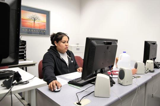 Four Corners Tax Help volunteer Tiffany Barbone helps prepare income tax paperwork Friday at the San Juan College Quality Center for Business.