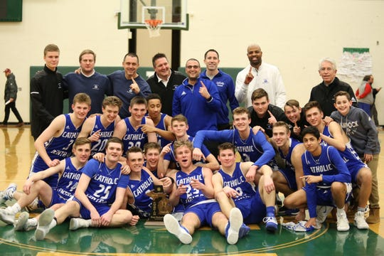 The Detroit Catholic Central basketball team celebrates its district title.