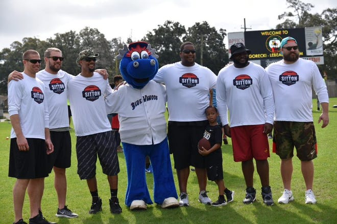 From left: Jordy Nelson, Ryan Taylor, Domenik Hixon, Fred Robbins, Ahtyba Rubin and Josh Sitton posee with Kazoo from the Pensacola Blue Wahoos during a camp hosted by Sitton on March 2, 2019.
