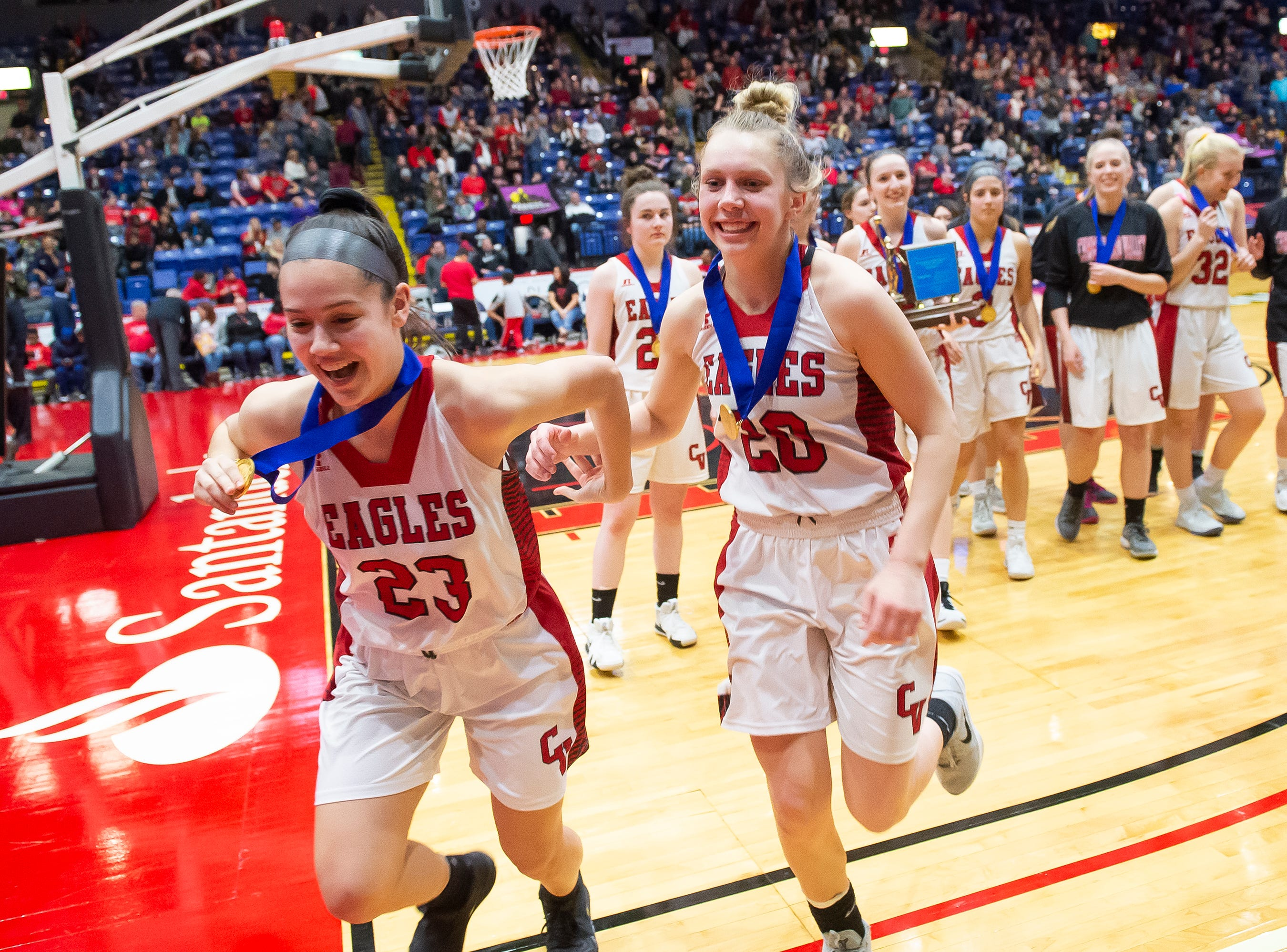 Cumberland Valley's Courtney Campbell (23) and Julie Jekot (20) run off the court with their gold medals after defeating Dallastown in the District 3 6A girls championship game at Santander Arena in Reading, Pa., Friday, March 1, 2019. The Eagles won 33-27.