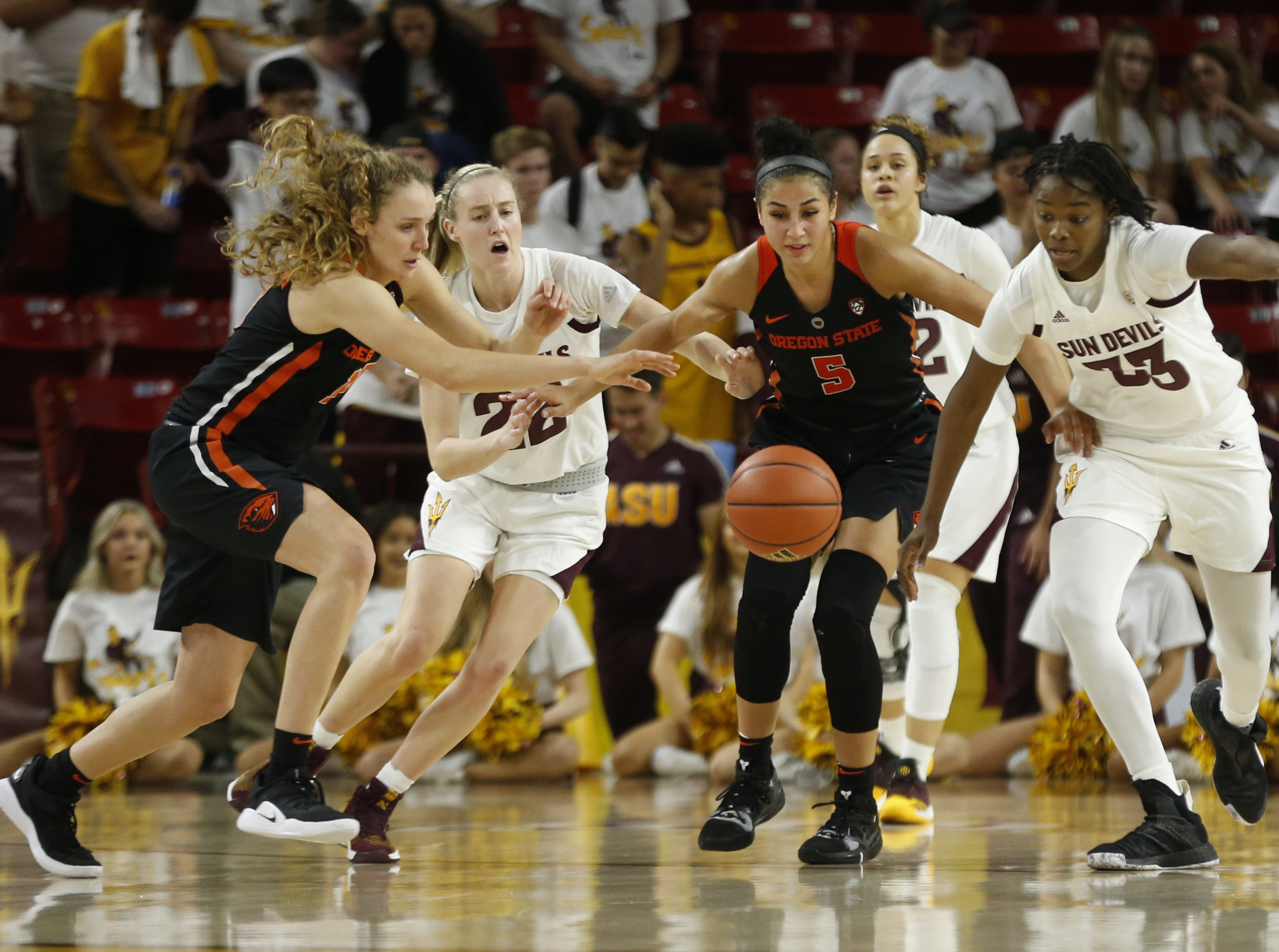 Oregon State's Katie McWilliams (10) and Taya Corosdale (5) scramble for a loose ball against ASU's Charnea Johnson-Chapman (33) and Courtney Ekmark (22) during the second half at Wells Fargo Arena in Tempe, Ariz. on March 1, 2019.