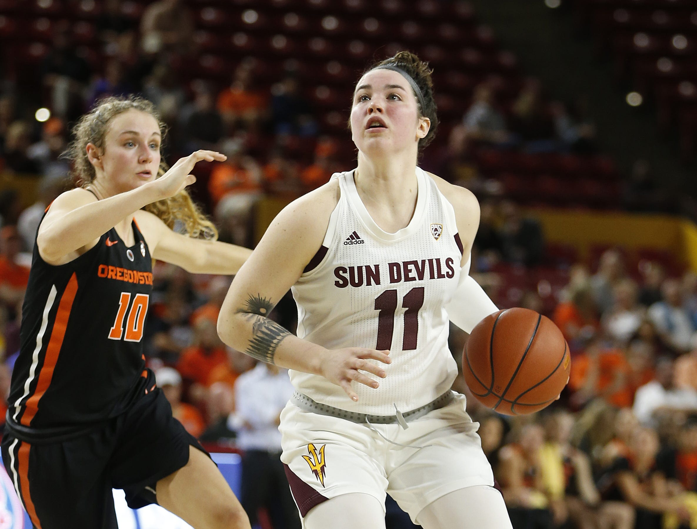 ASU's Robbi Ryan (11) dribbles into the lane against Oregon State's Katie McWilliams (10) during the second half at Wells Fargo Arena in Tempe, Ariz. on March 1, 2019.