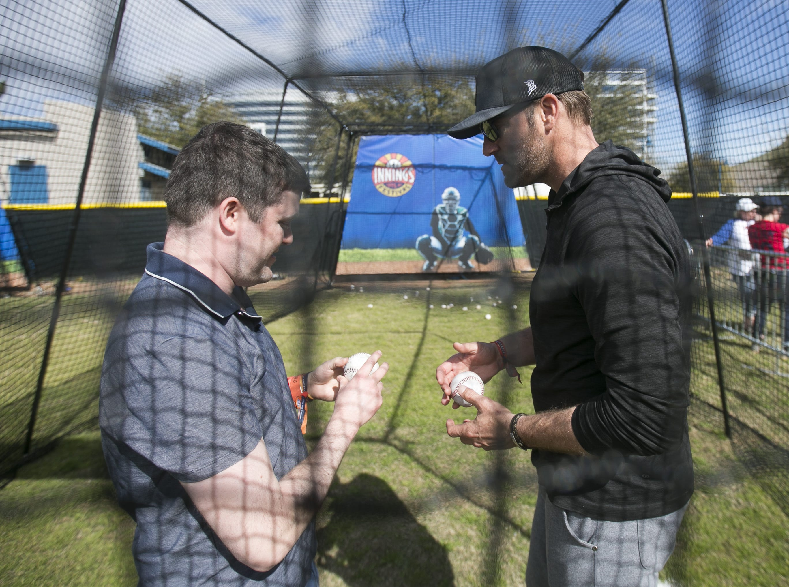 Former MLB pitcher Shawn Estes (right) shows Brian Wolther (left) pitching techniques at the Innings Festival at Tempe Beach Park on Saturday, March 2, 2019.