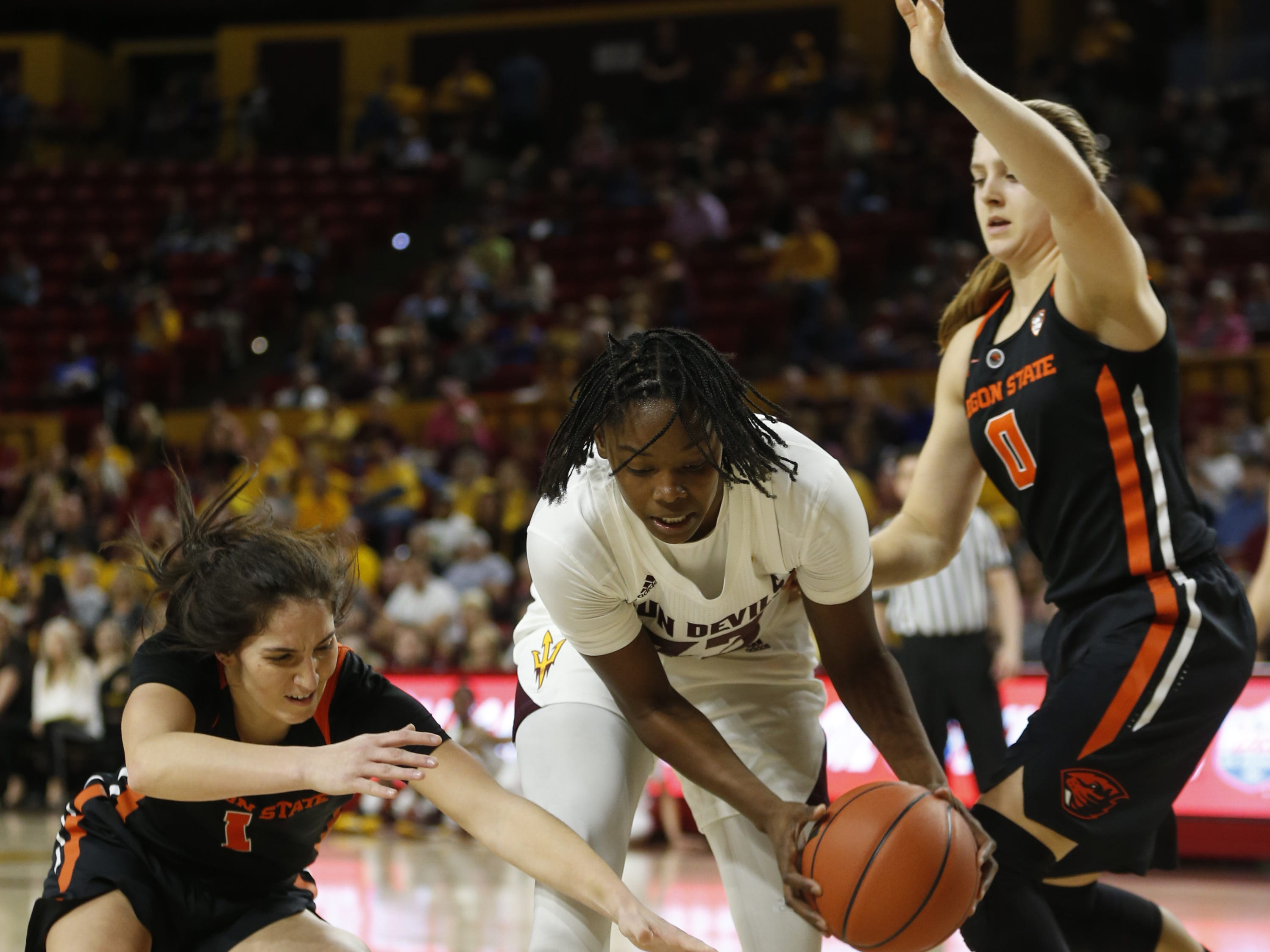 ASU's Charnea Johnson-Chapman (33) recovers a rebound against Oregon State's Mikayla Pivec (0) and Aleah Goodman (1) during the first half at Wells Fargo Arena in Tempe, Ariz. on March 1, 2019.