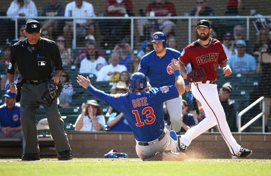 Chicago Cubs David Bote (13) slides across home plate scoring on a Kyle Schwarber RBI-single aganst the Arizona Diamondbacks in the first inning during a spring training game on Mar. 1, 2019 at Salt River Fields in Scottsdale, Ariz.