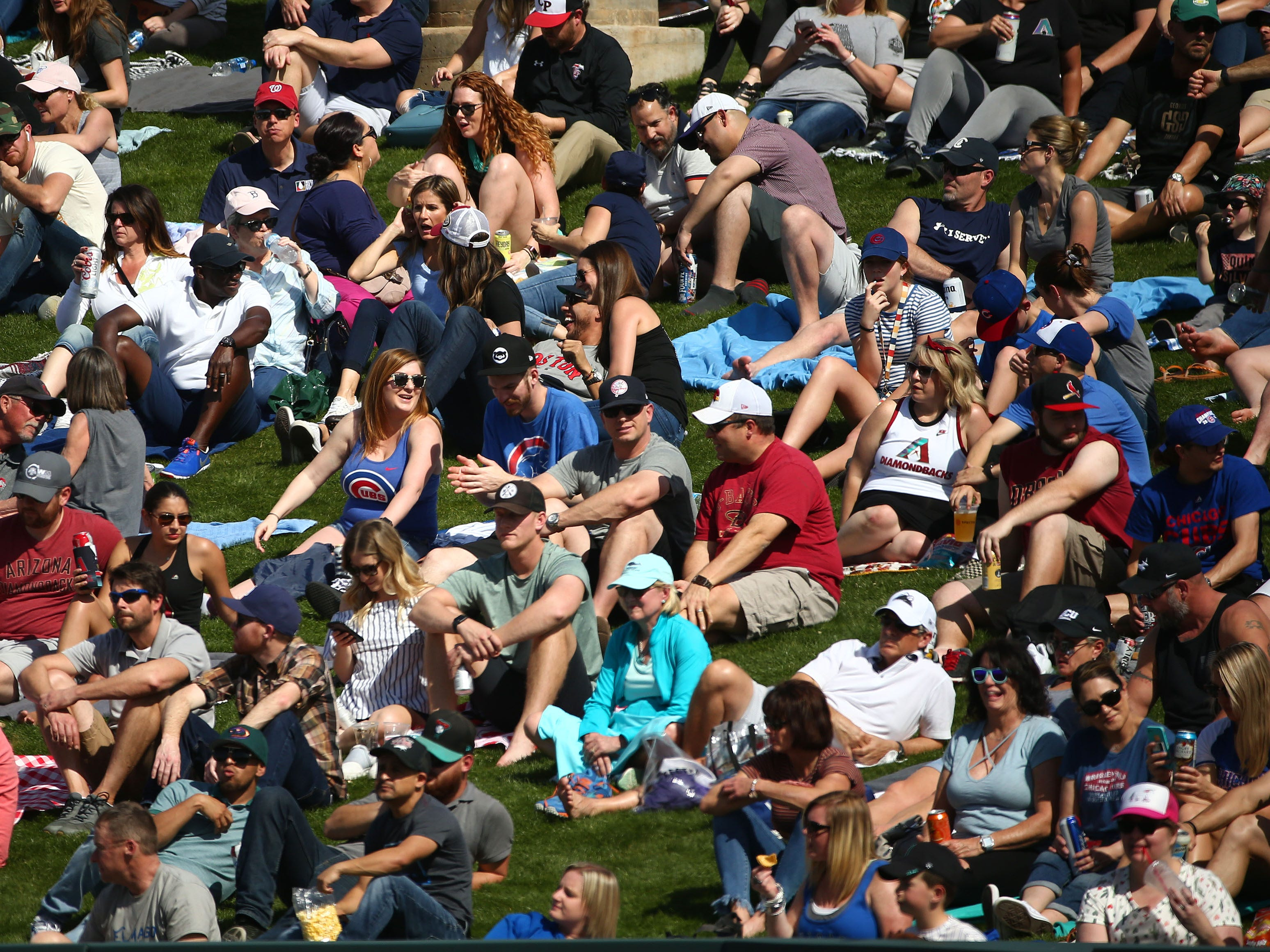 Fans crowd the outfield lawn as the Arizona Diamondbacks play the Chicago Cubs during a spring training game on Mar. 1, 2019 at Salt River Fields in Scottsdale, Ariz.