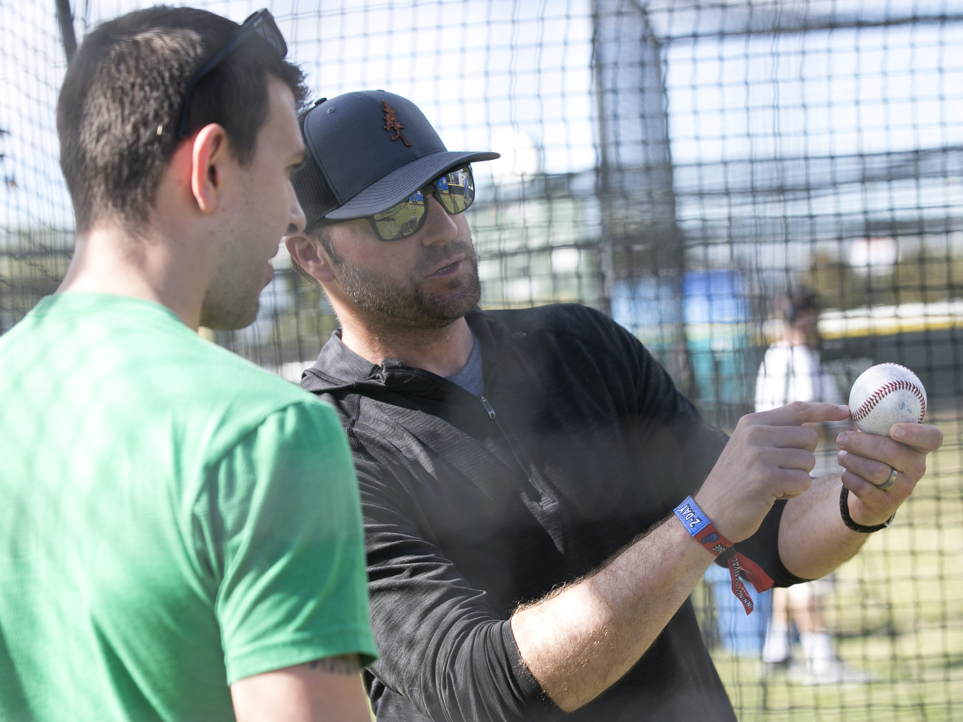 Former MLB pitcher Shawn Estes (right) shows Nick Luongo (left) pitching techniques at the Innings Festival at Tempe Beach Park on Saturday, March 2, 2019.