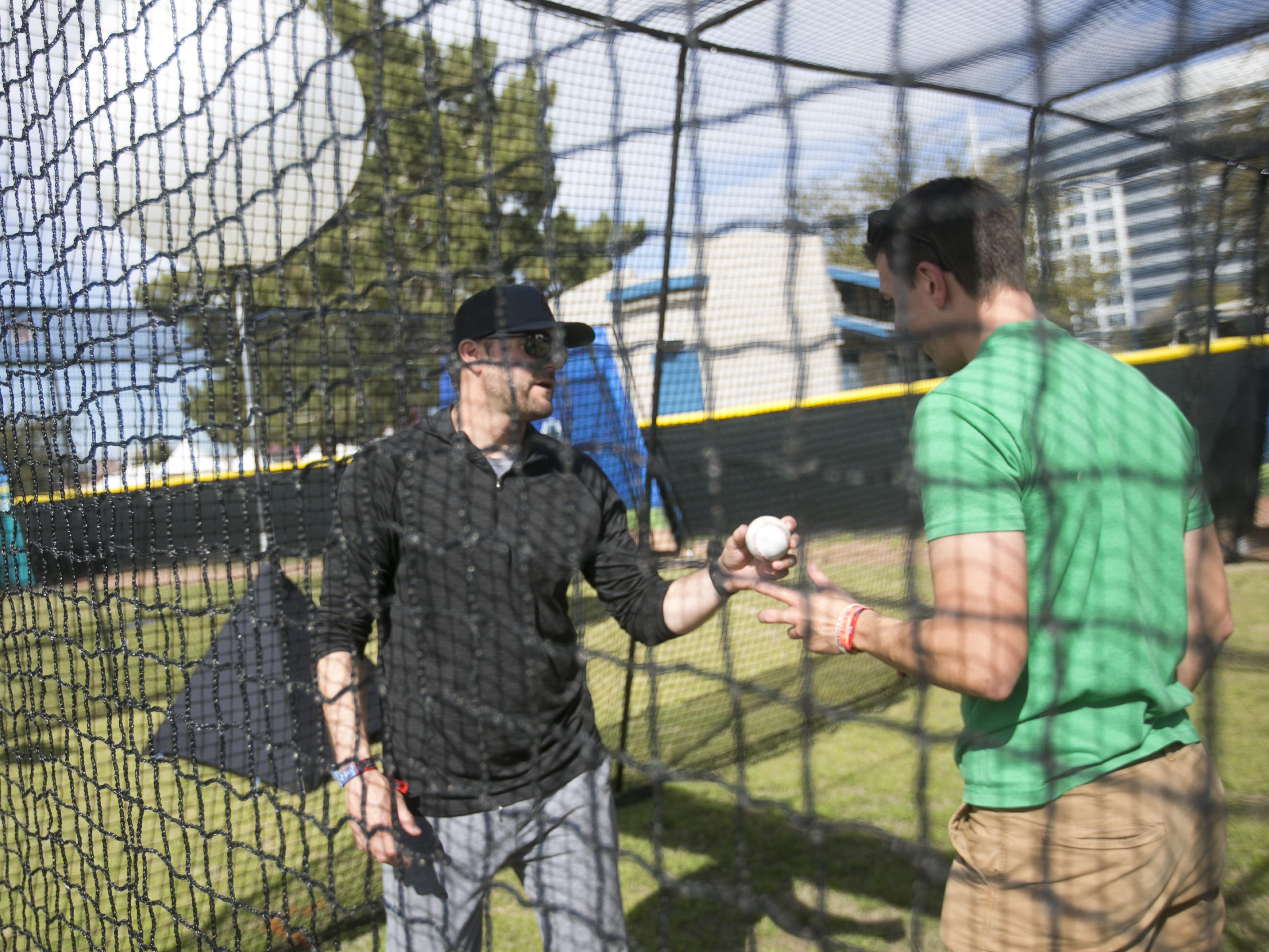Former MLB pitcher Shawn Estes (left) shows Nick Luongo (right) pitching techniques at the Innings Festival at Tempe Beach Park on Saturday, March 2, 2019.