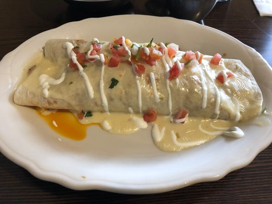 The author's personal favorite, the Burrito San Jose with grilled chicken, chorizo, rice and beans, topped with pico de gallo, sour cream and Plaza Azteca's delicious cheese sauce. This is two meals in one!