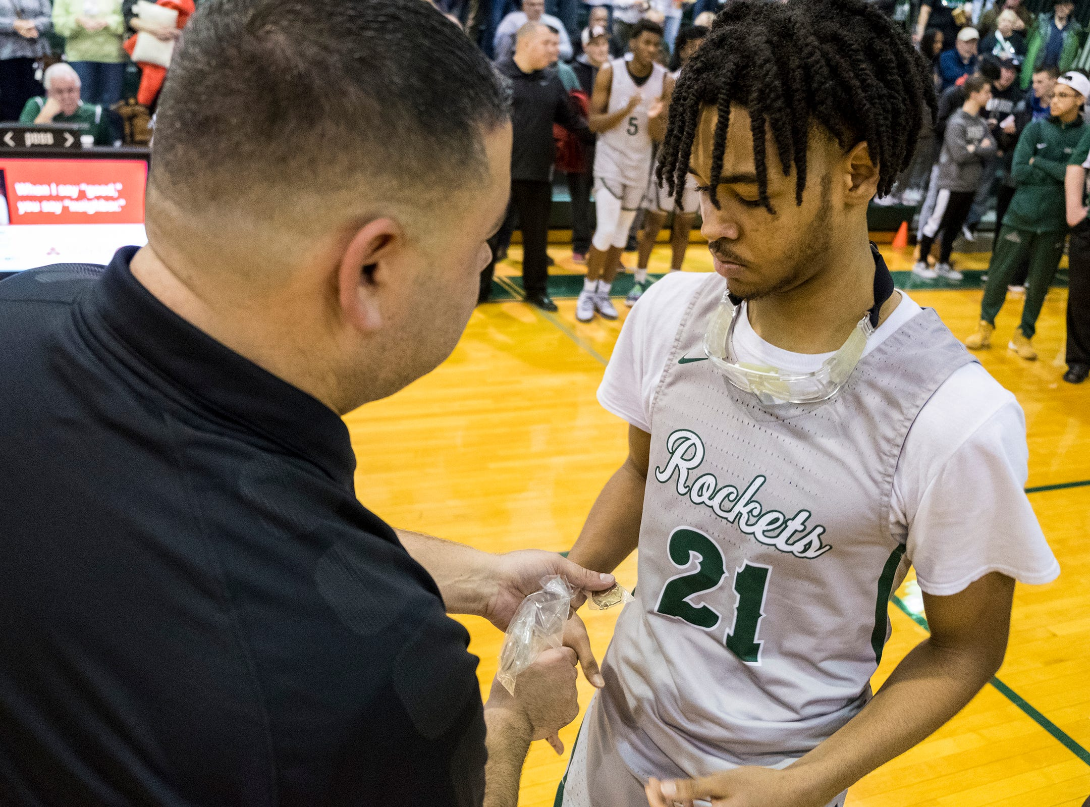 New Haven athletic director Orlando Medina (left) hands a championship medal to guard Jamir Farrior during the MHSAA Division 2 Boys Basketball District Finals Friday, March 1, 2019 at New Haven High School.