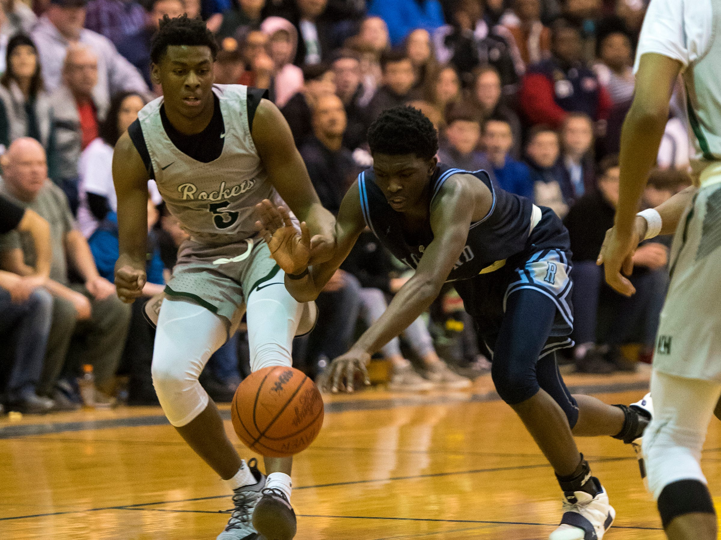 Richmond High School guard Daveyon Henderson (right) and New Haven guard Trenell Payne chase a loose ball during the MHSAA Division 2 Boys Basketball District Finals Friday, March 1, 2019 at New Haven High School.