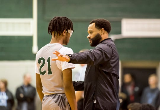 New Haven head coach Tedaro France II talks with guard Jamir Farrior during the MHSAA Division 2 Boys Basketball District Finals against Richmond High School Friday, March 1, 2019 at New Haven High School.