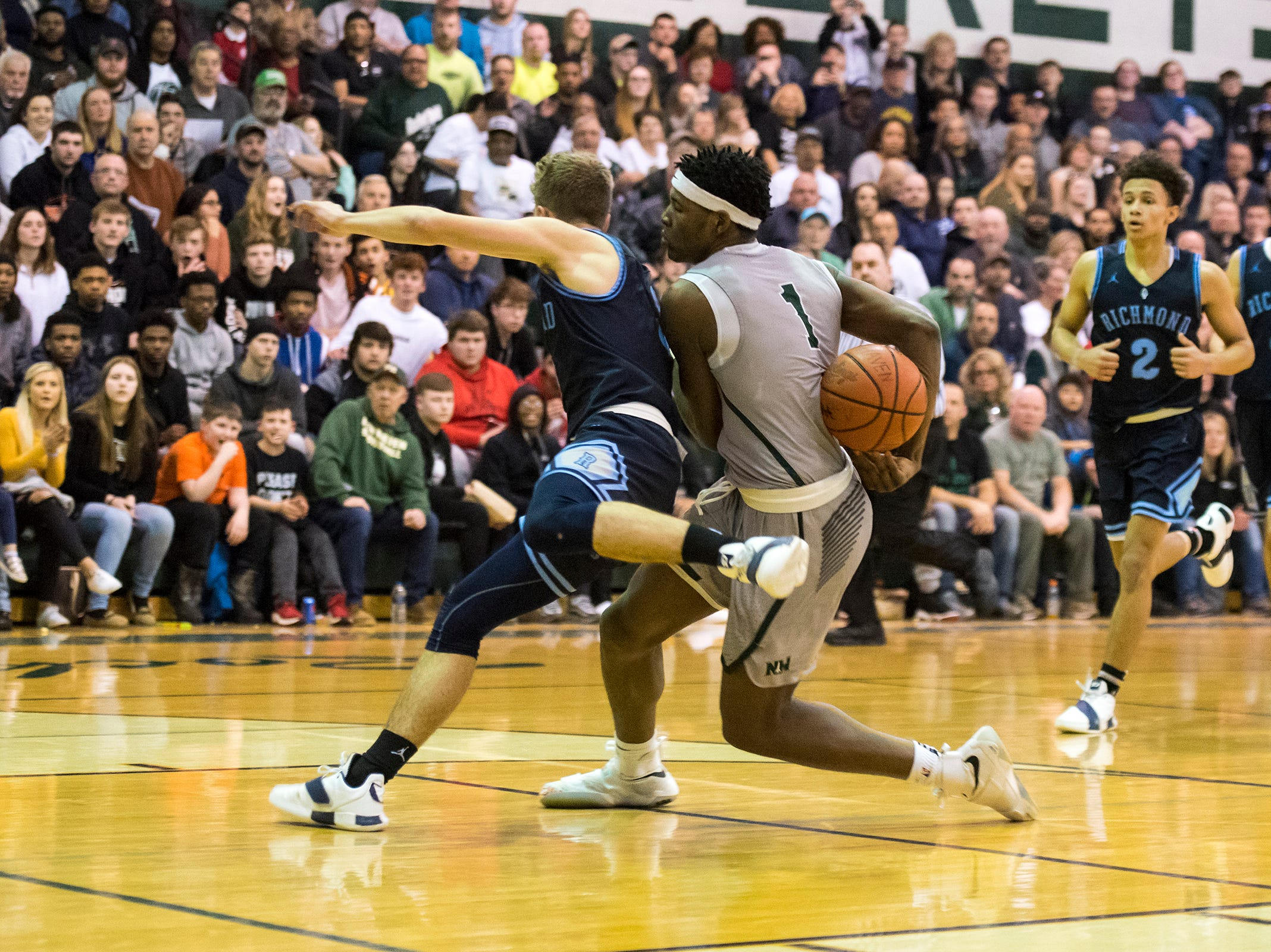 New Haven forward Romeo Weems (1) pushes into Richmond High School guard Jackson Allen during the MHSAA Division 2 Boys Basketball District Finals Friday, March 1, 2019 at New Haven High School.