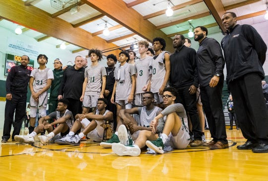 The New Haven High School basketball team pose for a photo with the MHSAA Division 2 Boys Basketball District Finals trophy after defeating Richmond High School 92-53 Friday, March 1, 2019 at New Haven High School.