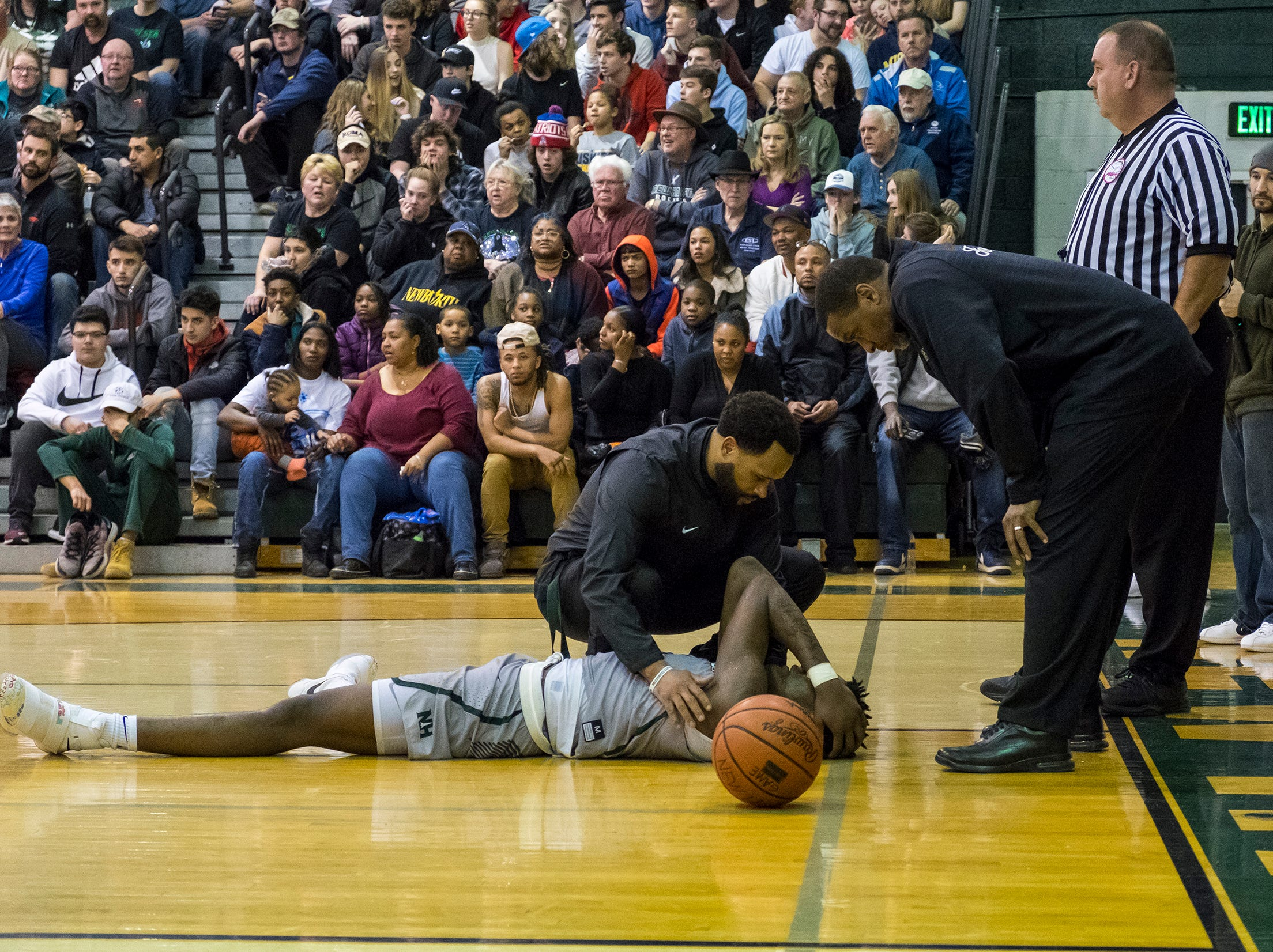 New Haven coaching staff tend to forward Romeo Weems after he hits the ground hard during the MHSAA Division 2 Boys Basketball District Finals against Richmond High School Friday, March 1, 2019 at New Haven High School.