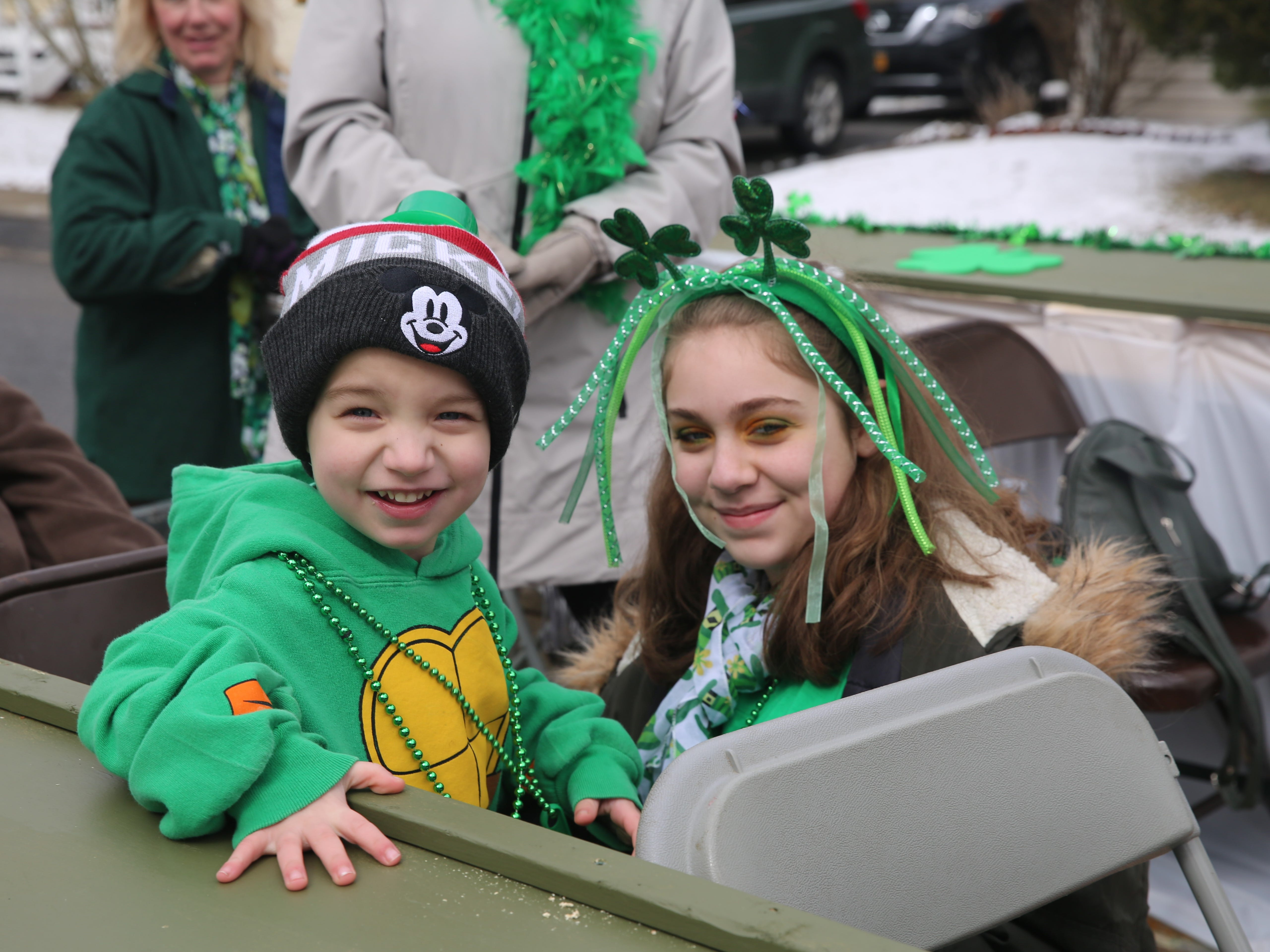 Fishkill residents Cairra Marico (right), 12, and Jayden Wetzelberger, 4, smile from a float in Saturday's Dutchess County St. Patrick's Day Parade. Thousands of people showed up to the event, which shut down West Main Street and other parts of Wappingers Falls on Saturday.