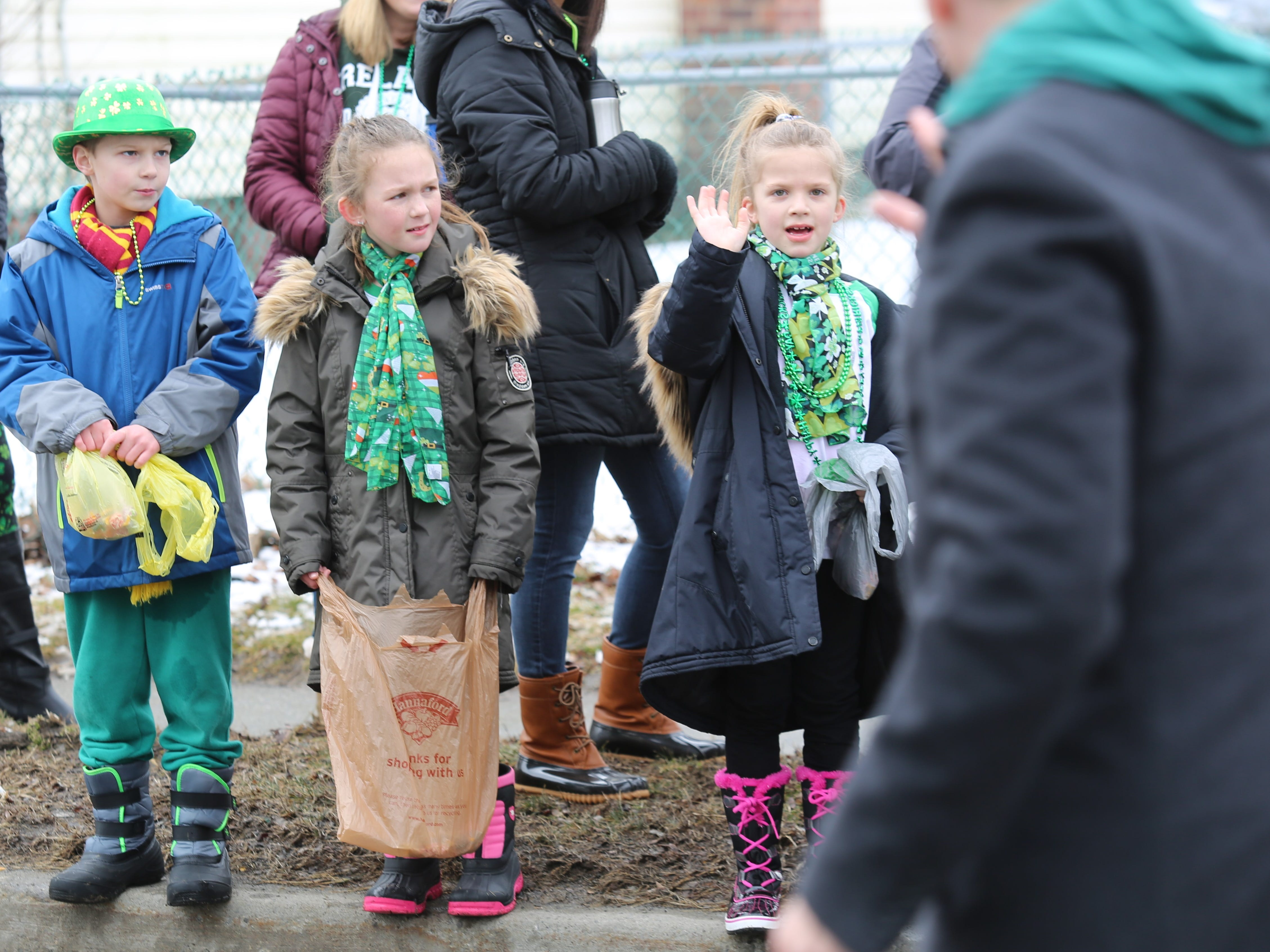 (from left to right) Derek Cogan, 8, Aubrey Cerone, 9, and Braelynn Cerone, 7, watch the Dutchess County St. Patrick's Day Parade pass by in Wappingers Falls on Saturday.
