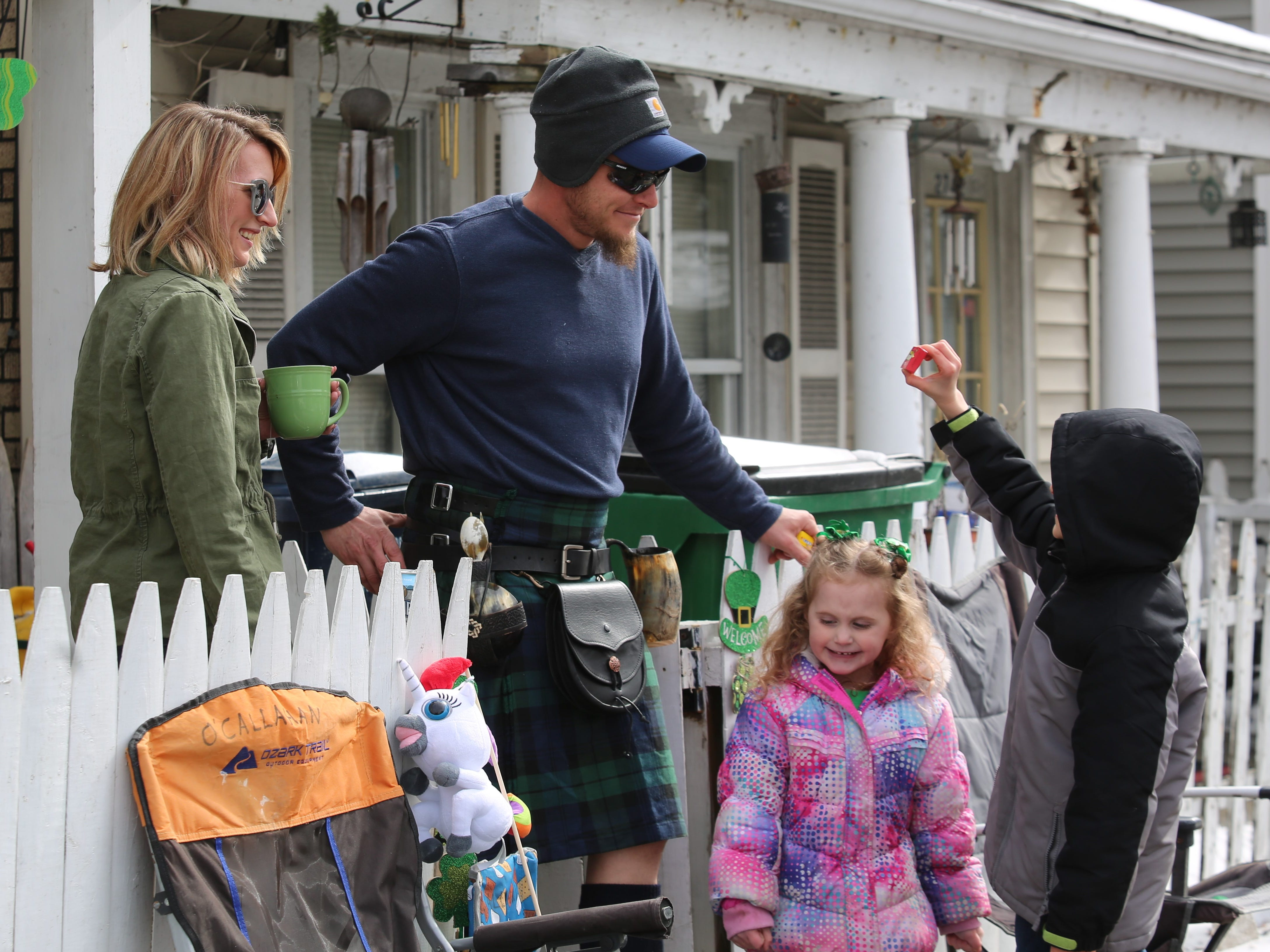 Heather O'Callahan (left) and Dan Callahan (left center) look on as their son, Danny O'Callahan (right), 8, shows off his candy and daughter, Lilly O'Callahan (right center), 5, smiles during the 24th annual Dutchess County St. Patrick's Day Parade on Saturday. Their home is right along the parade route, so each year they come outside to watch.