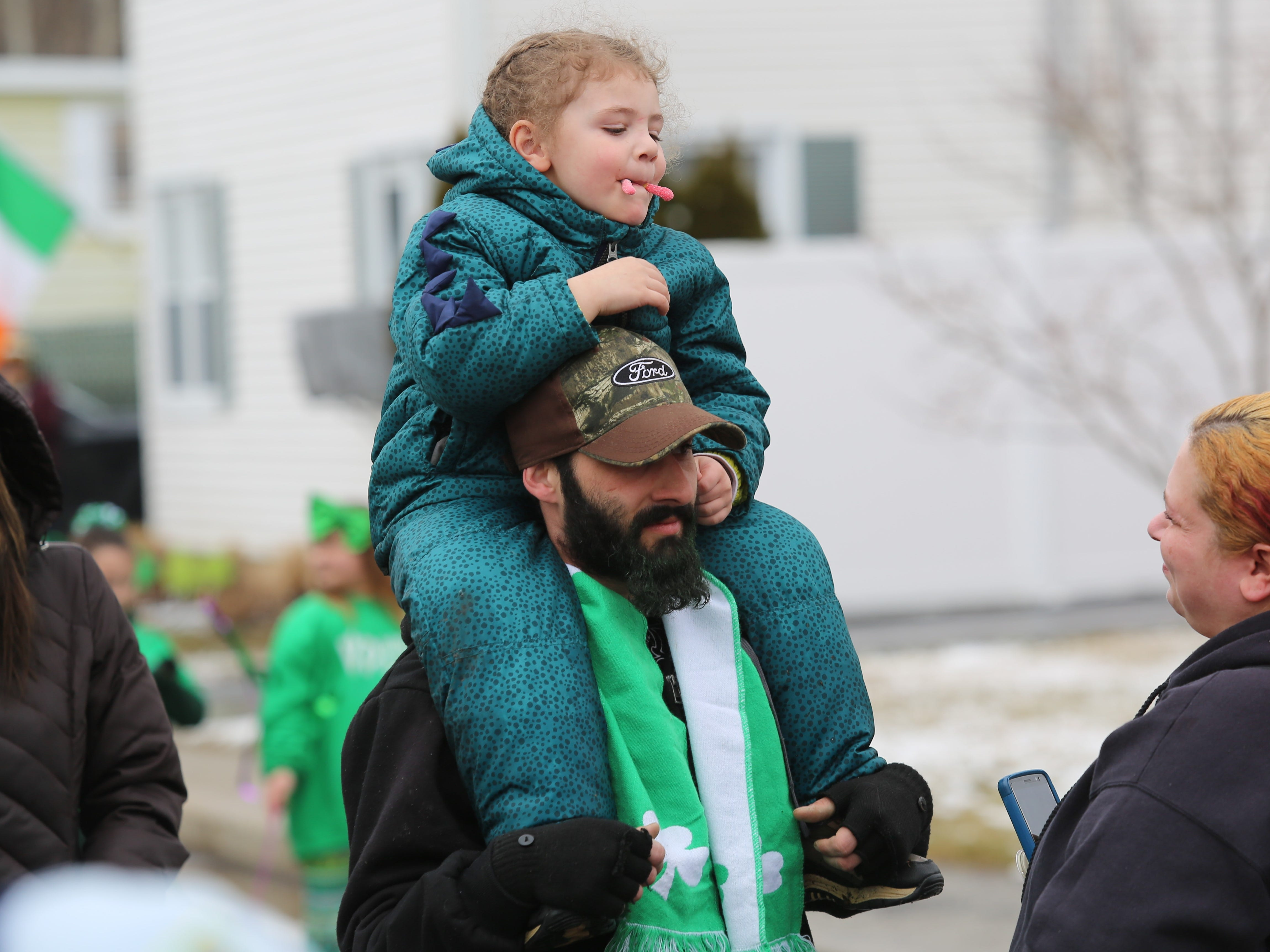 Joanie Kitzweger (right) looks on as Michael Ruseskas, 4, eats a gummy worm sitting on the shoulders of his father, Michael Ruseskas, before the Dutchess County St. Patrick's Day Parade on Saturday.