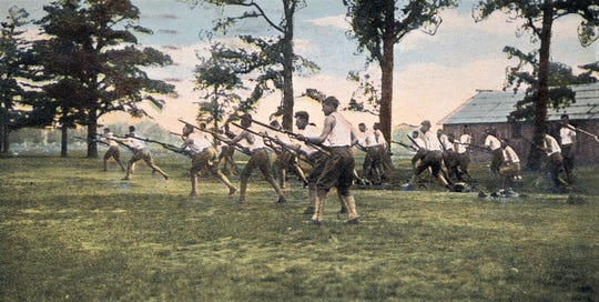 Postcard sent home by Lawrence Funk showing soldiers doing a bayonet drill at Camp Gordon in 1917