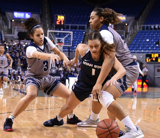 Nevada's Essence Booker, left and Emma Torbert double-team Utah State's Eliza West late in Saturday's game at Lawlor Events Center. Nevada lost 71-59.