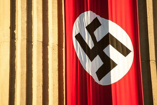 Stock image of swastika flag hanging on building.