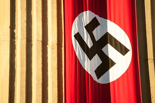 Stock image of swastika flag hanging on building.