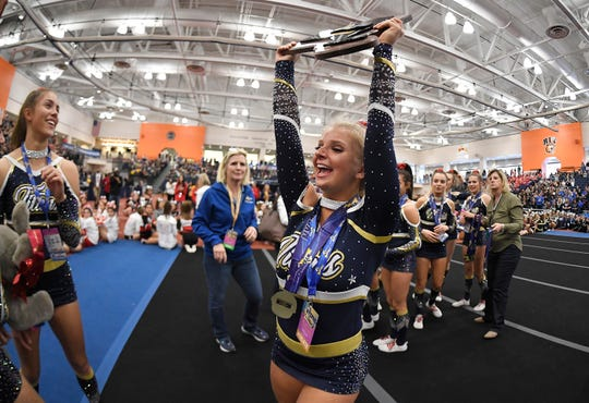 Webster Thomas' Alyssa Cala raises the championship plaque after the Titans won first place in the Co-Ed Division during the NYSPHSAA Cheerleading Championships Saturday at RIT.