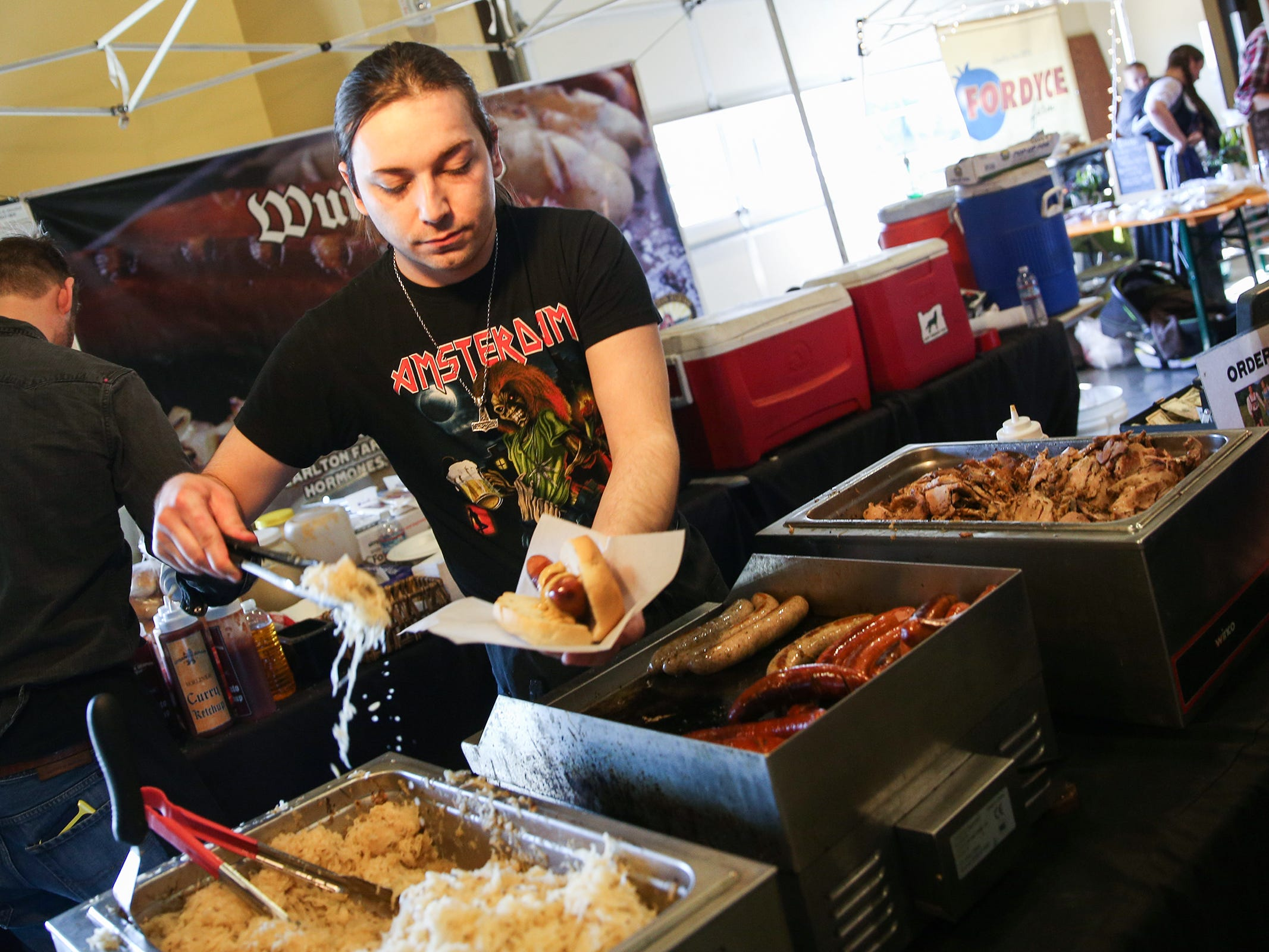 Josh Northcutt, of Portland based Urban German Grill, serves a plate during the annual Volksfest in Mt. Angel on Saturday, March 2, 2019.