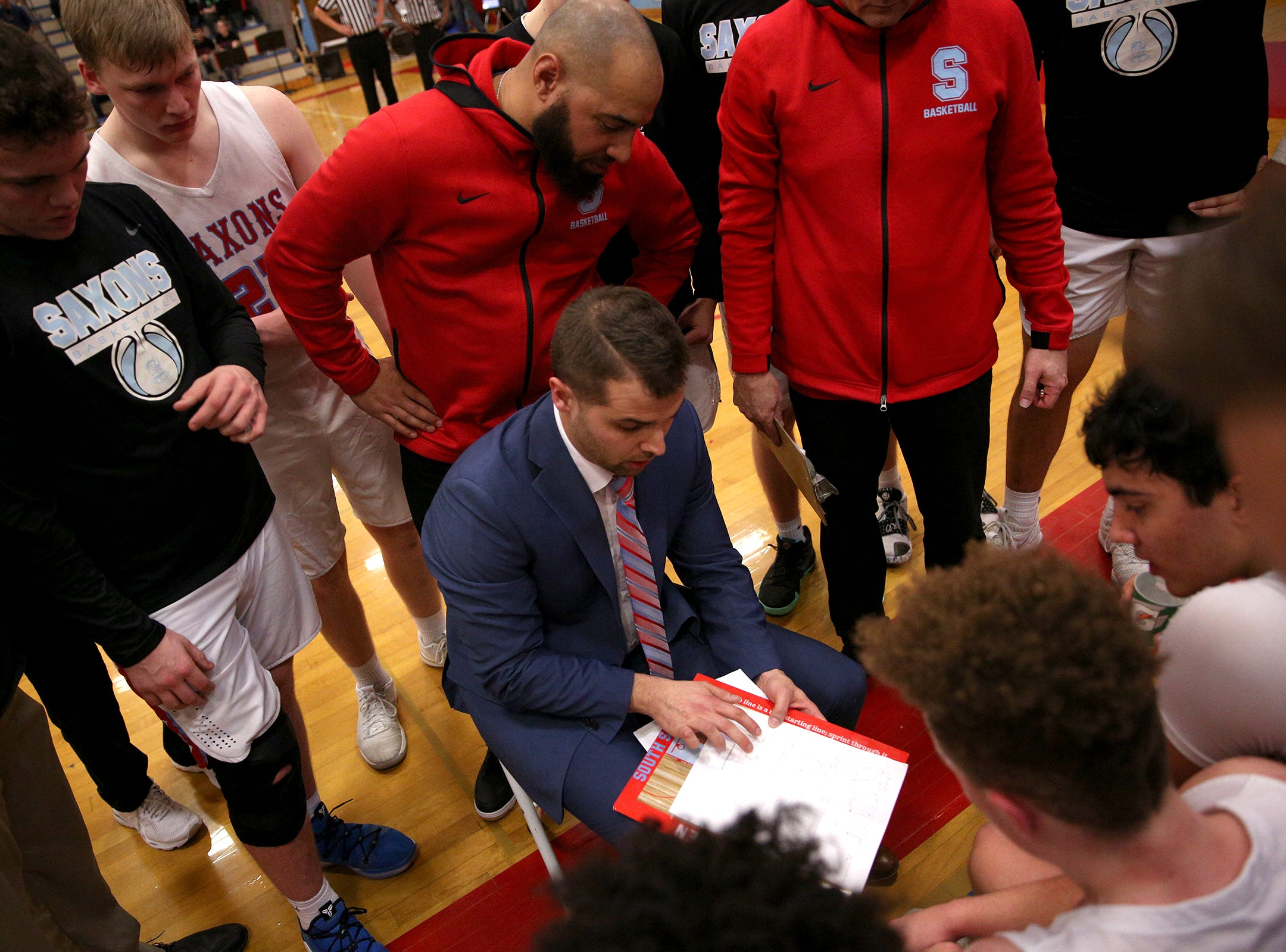 South Salem's head coach Tyler Allen goes over a play with his team during the South Salem vs. West Linn boys basketball OSAA playoff game at South Salem High School on Friday, March 1, 2019.