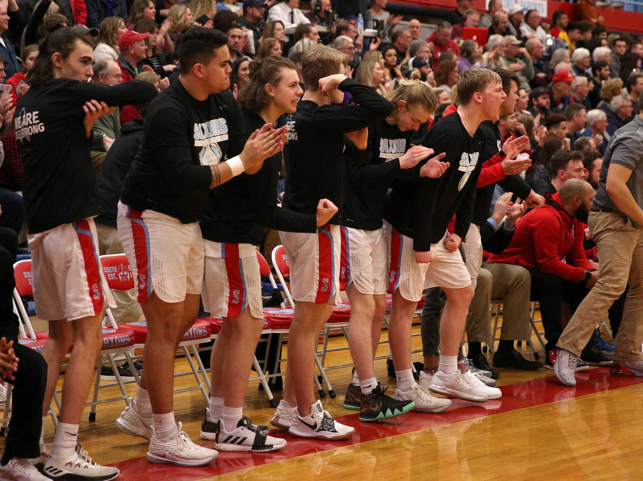 South Salem teammates cheer on their team from the bench during the South Salem vs. West Linn boys basketball OSAA playoff game at South Salem High School on Friday, March 1, 2019.