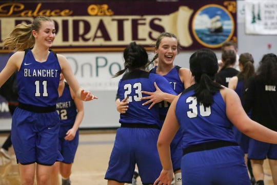 From left: Blanchet Catholic's Trinity Phipps (11), Ana Coronado (23), Hailey Ostby (21) and Kalea Salang (30) celebrate their win against Salem Academy after the girls 3A state basketball semifinal game at Marshfield High School on Friday, March 1.