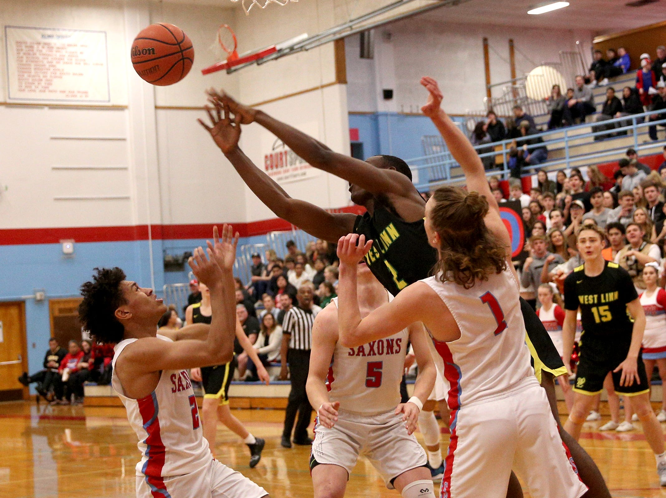 South Salem and West Linn teammates struggle to gain control of the ball during the South Salem vs. West Linn boys basketball OSAA playoff game at South Salem High School on Friday, March 1, 2019.
