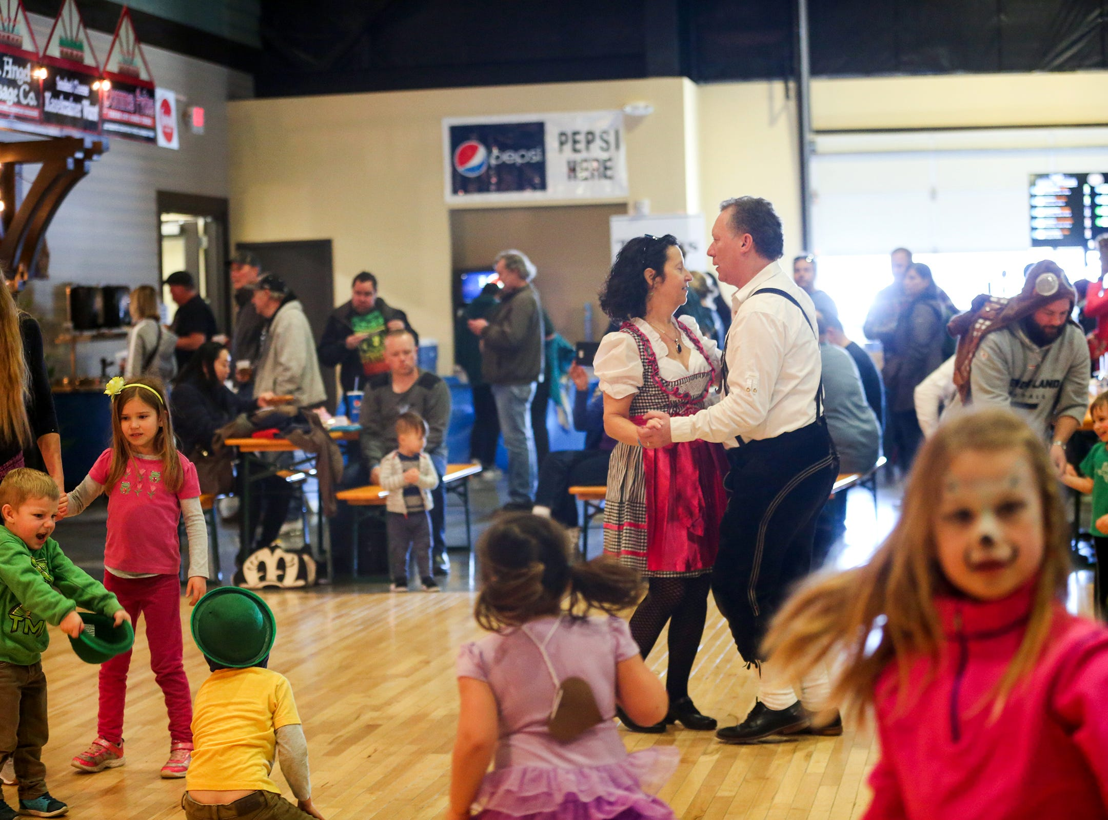 Moira Lieberson and Jeff Hamling dance around children at the annual Volksfest in Mt. Angel on Saturday, March 2, 2019. The kids area had games and face painting.