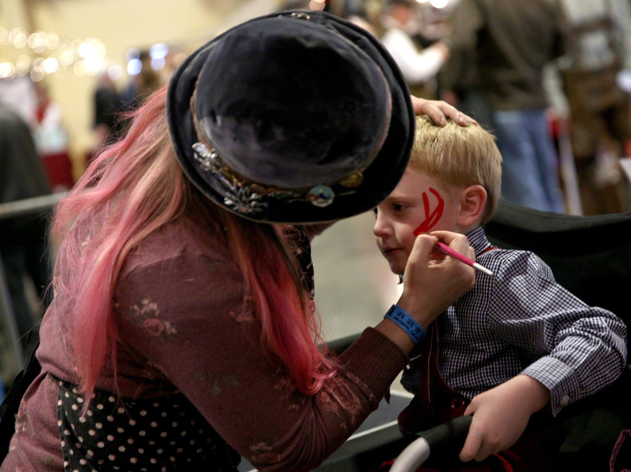 Face and body painter Andrea McClintock freestyle paints on Christopher Wright, 4, in the kids section of Volksfest in Mt. Angel on Saturday, March 2, 2019.
