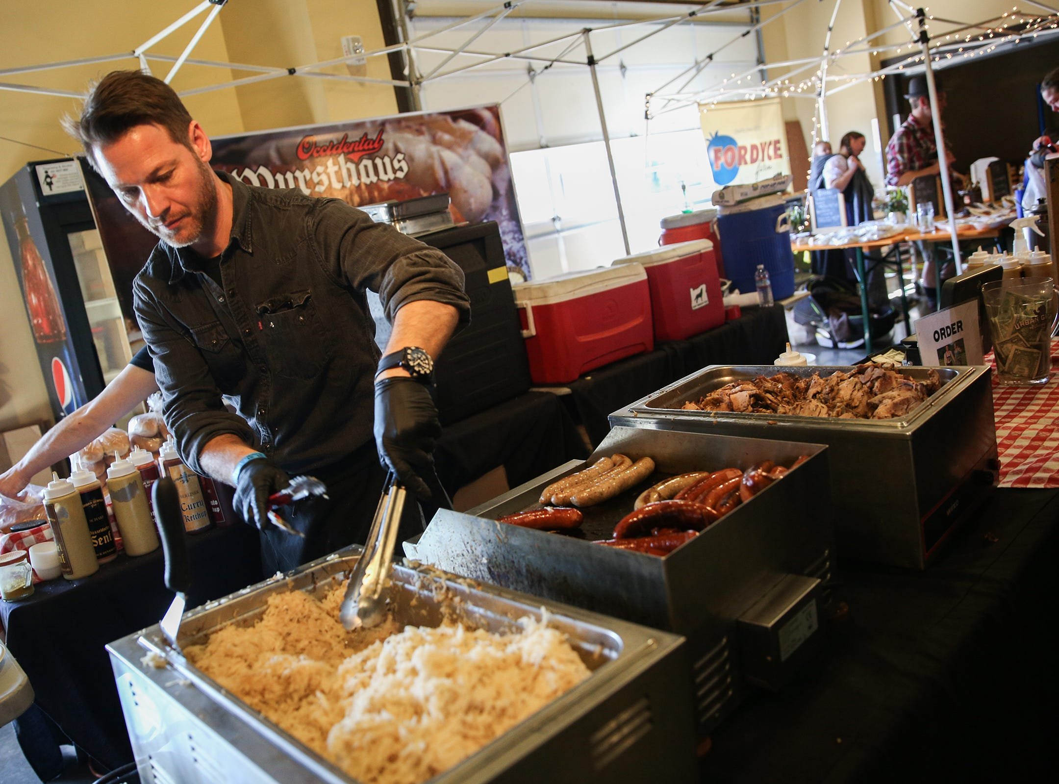 David Gluth, of Portland based Urban German Grill, serves a plate during the annual Volksfest in Mt. Angel on Saturday, March 2, 2019.