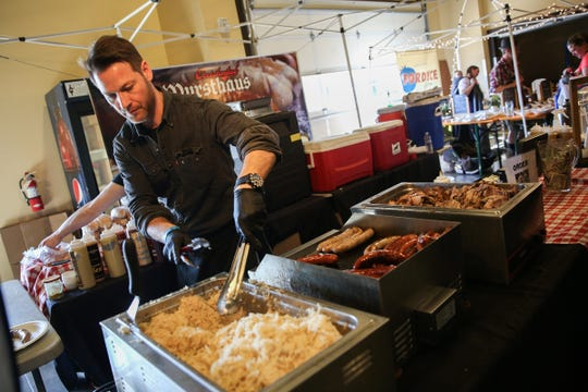 David Gluth, of Portland based Urban German Grill, serves a plate during Volksfest in Mt. Angel on March 2, 2019.