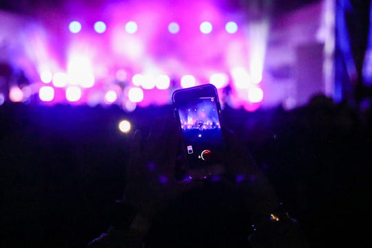 A fan takes a photo of Flatland Cavalry performing during Wild West Fest Friday, March 1, 2019, at the Bill Aylor Sr. Memorial RiverStage.