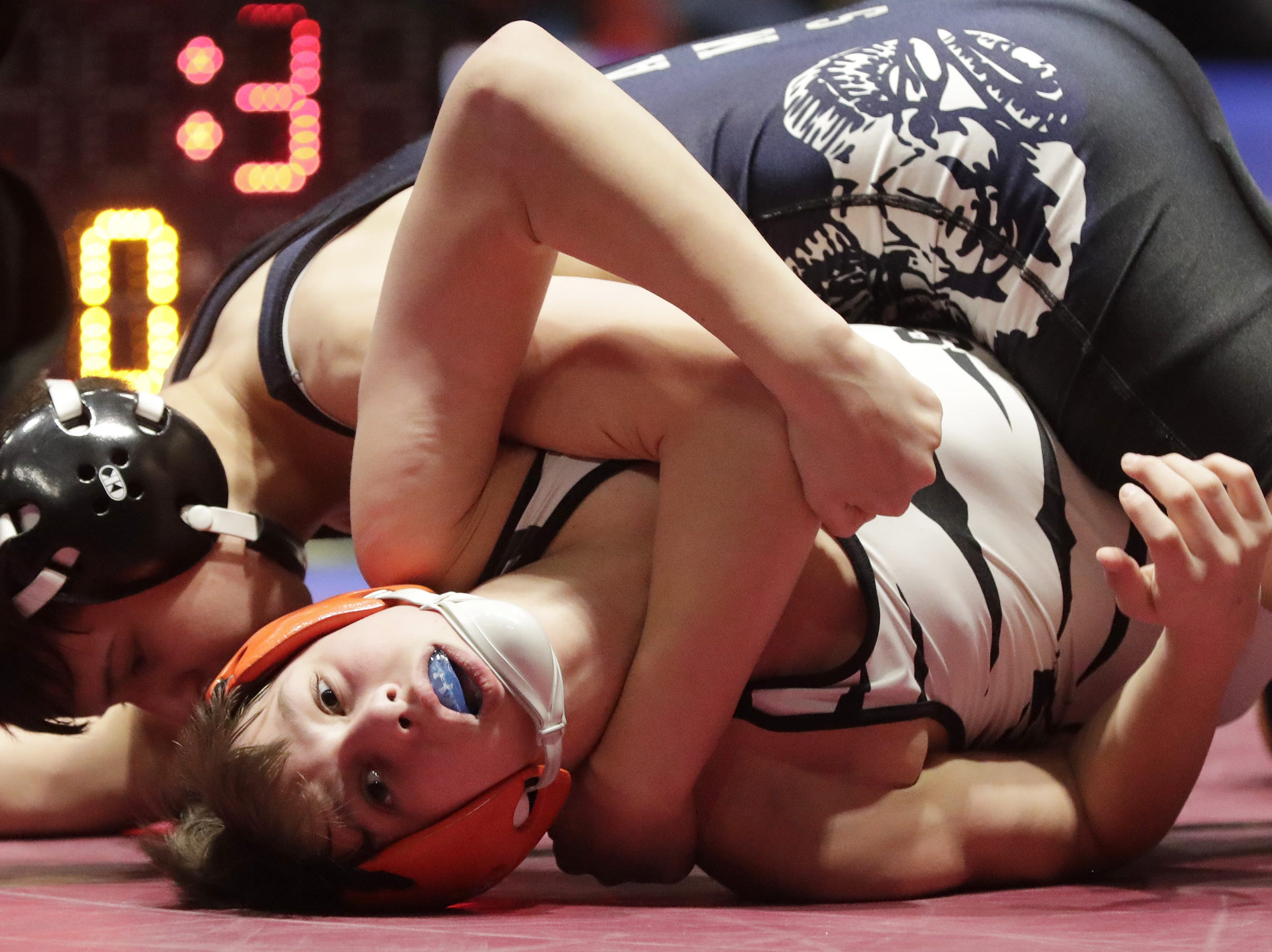 Stratford's Logan Gaulke, left, looks from the mat as Random Lake's Tanner Bierenbaum controls him in a 106-pound match, Saturday, March 2, 2019, in Madison, Wis.