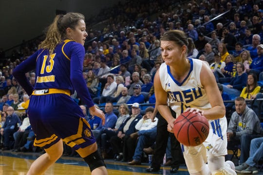 SDSU's Macy Miller (12) dribbles the ball past Western Illinois's Olivia Kaufmann (13) during a game, Saturday, March 2, 2019 in Brookings, S.D.