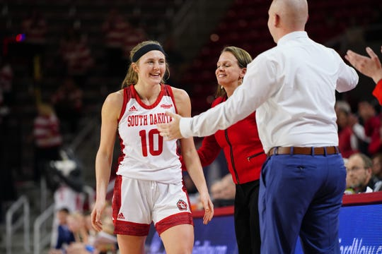 South Dakota senior Allison Arens is greeted by her coaches as she subs out for the final time at the Sanford Coyote Sports Complex. Arens finished with 18 points in the final home game of her career.