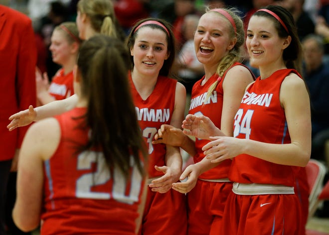 Wausau Newman's Lauren Shields (23), Mackenzie Krach (12) and Julia Seidel (34) celebrate during last year's WIAA girls basketball playoffs.