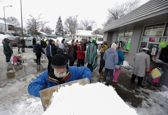 Local artist Jef Schobert builds a snow sculpture as patrons wait in line for ice cream on Friday, March 1, 2019, at Belts' Soft Serve in Stevens Point. The stand opened for the season on Friday.